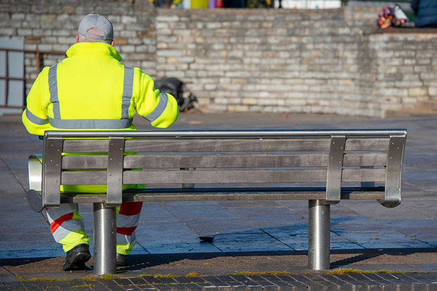 street cleaner wearing hi vis jacket and trousers has a quick coffee or tea break whilst sitting on a bench